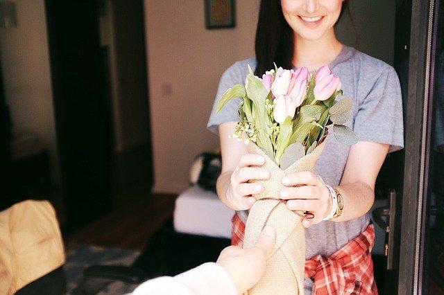 uśmiechnięta brunetka w rozpuszczonych włosach trzyma bukiet kwiatów