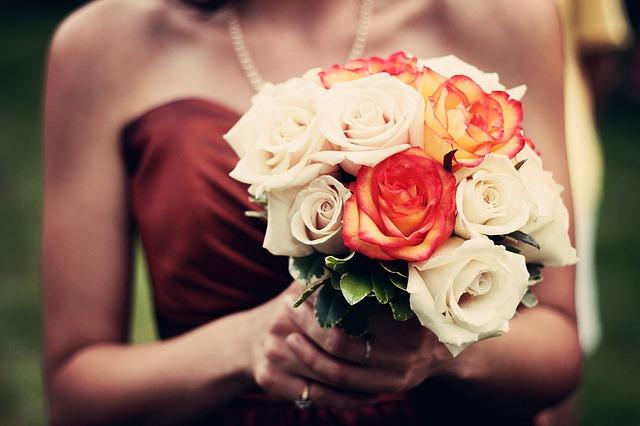 zbliżenie na kobiece dłonie, w których znajduje się bukiet herbacianych róż