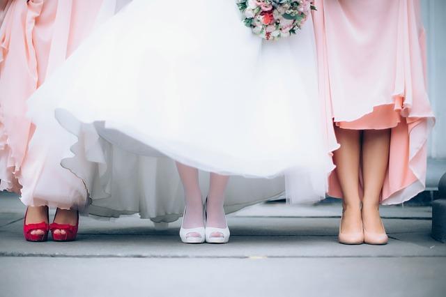 zbliżenie na nogi panny młodej w białej sukni i białych rajstopach oraz na druhny ubrane na różowo
