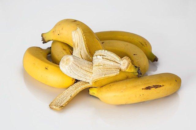 jeden obrany banan leżący na kilku innych nieobranych
