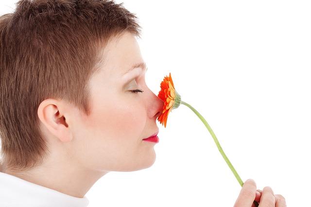 prawy profil kobiety  z krótkimi włosami, która w dłoni trzyma kwiatka