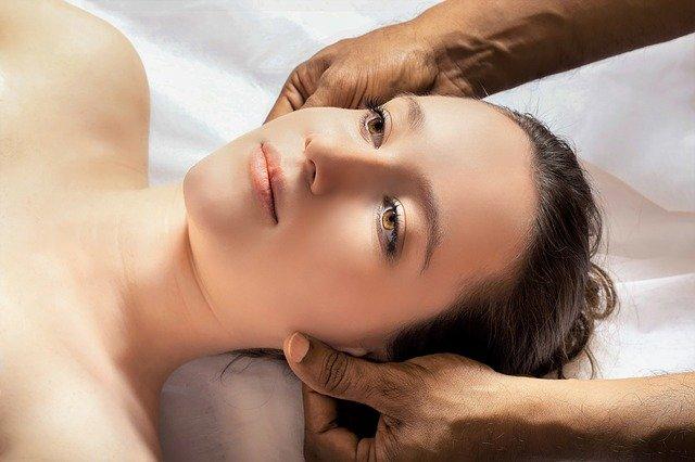 głowa kobiety masowana przez męskie dłonie