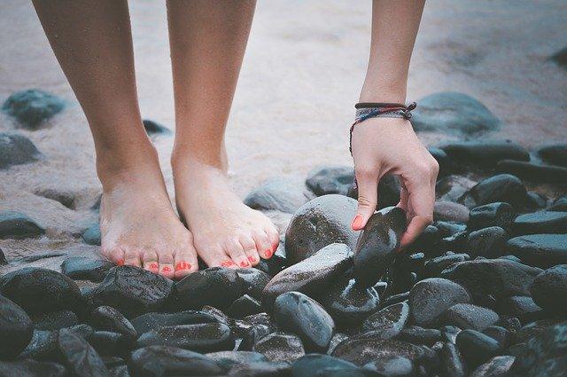 kobiece stopy z różowymi paznokciami stoją na czarnych kamieniach