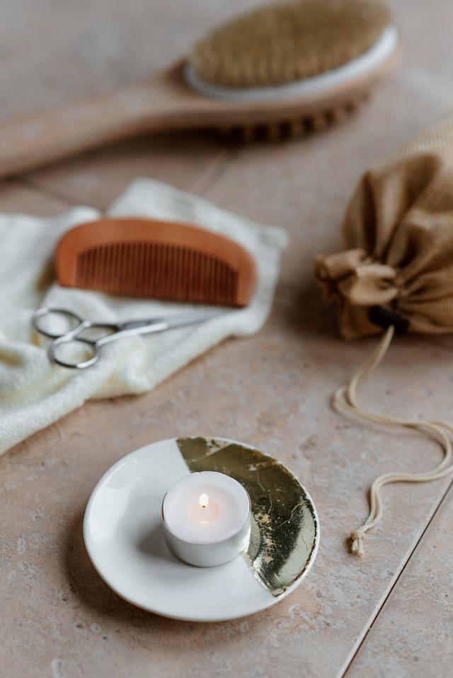 świeczka na małym talerzyku obok drewnianego grzebienie i małego woreczka