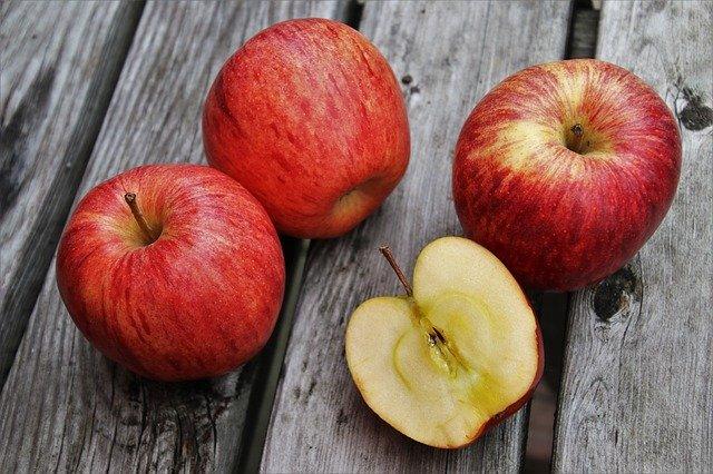 czerwone jabłka leżące na drewnie