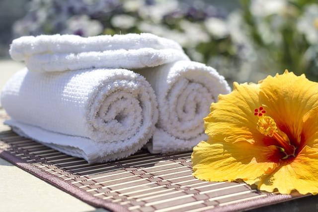 zwinięte białe ręczniki a przed nim leży żółty kwiat