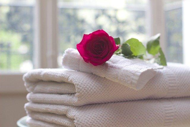 białe, złożone ręczniki ułożone jeden na drugim, a na górze leży czerwona róża