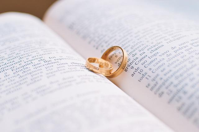 dwie złote obrączki włożone w środek książki