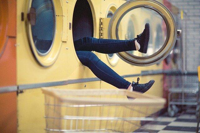 wystające kobiece nogi z pralki w miejskiej pralni