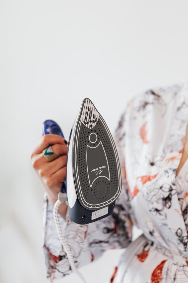 kobieta trzyma w dłoni żelazko