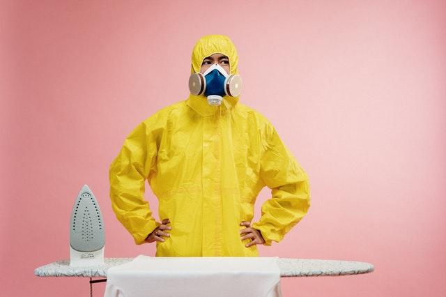 osoba ubrana w maskę i żółty strój ochronny stoi na różowym tle przy desce do prasowania