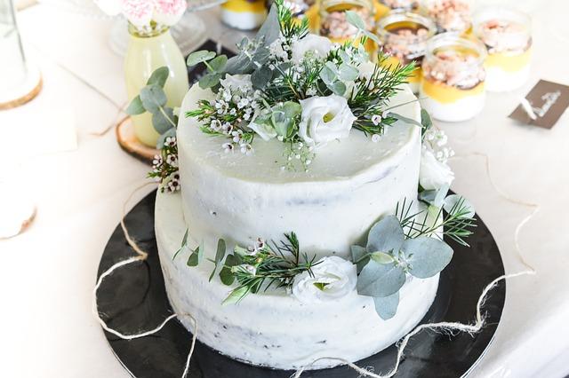 piętrowy jasny tort z wyłożonymi na nim szarymi i niebieskimi kwiatami