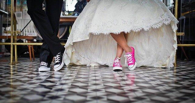 zbliżenie na nogi kobiety w białej sukni ślubnej i różowych trampkach, obok której stoi mężczyzna w czarnym garniturze i ma także czarne trampki