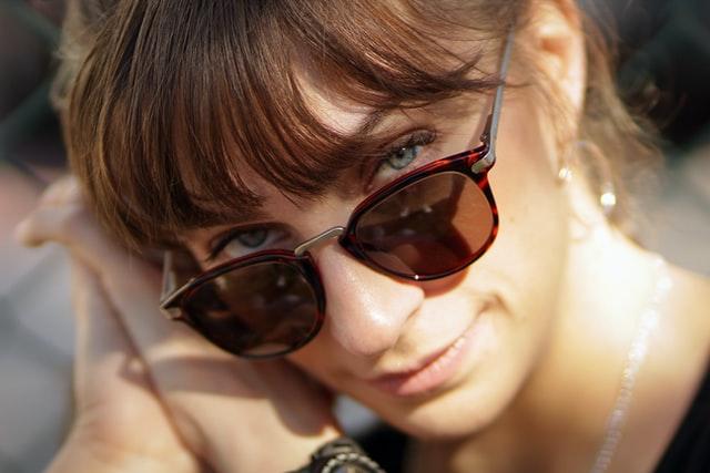 zbliżenie na twarz kobiety z grzywką w okularach przeciwsłonecznych