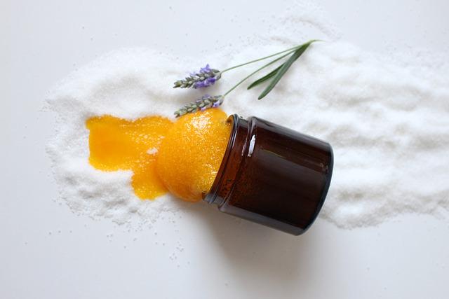 miód wymieszany z solą wylewa się z brązowego słoiczka na biały blat