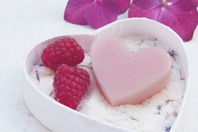 maliny i różowe mydło położone na pojemniku