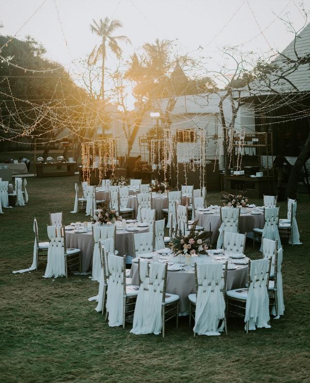 białe stole weselne i krzesła rozstawione w ogrodzie