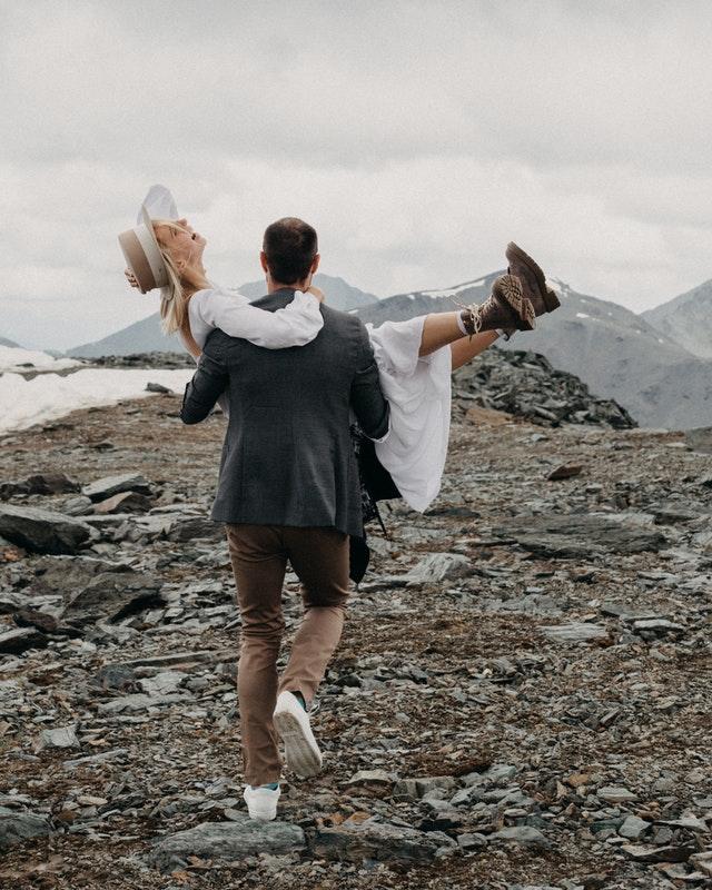 mężczyzna niesie kobietę w sukni ślubnej na rękach po górach