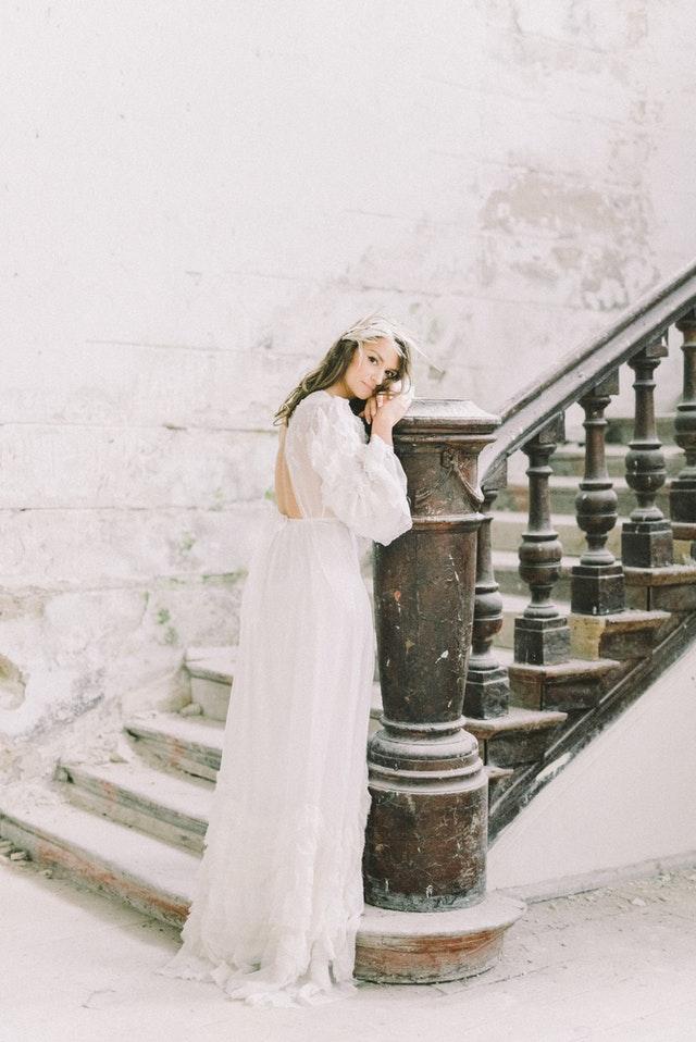 kobieta w białej sukni opiera się o balustradę na schodach