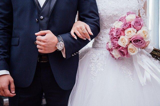 kobieta w sukni ślubnej pod ręką z mężczyzną w czarnym garniturze