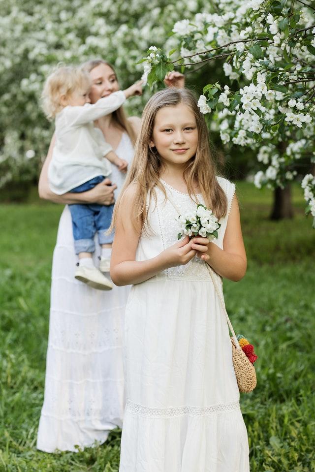 dziewczynka w białej sukni a za nią stoi kobieta w białej kreacji i trzyma dziecko na tle sadu