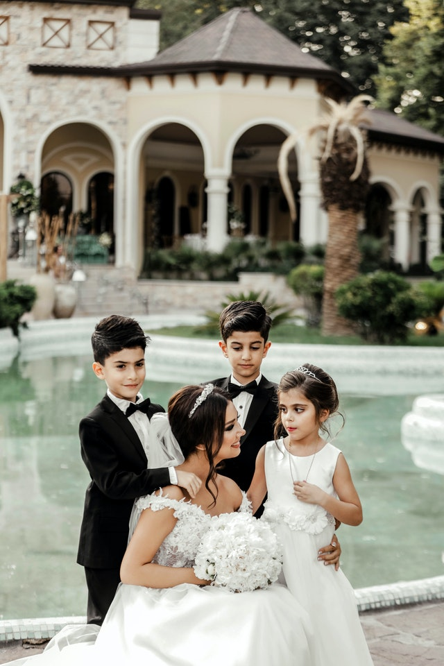 panna młoda w białej sukni w otoczeniu odświętnie ubranych dzieci