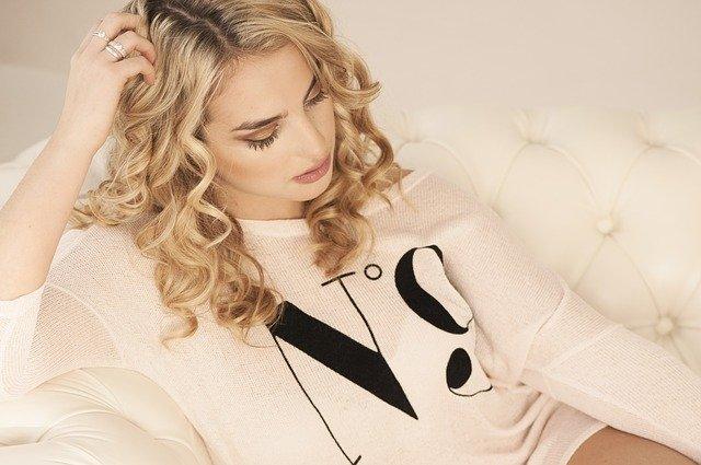 ubrana na biało blondynka z kręconymi włosami  patrzy w dół