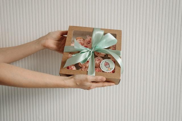 prezent zawinięty w niebieską wstążkę trzymany w dłoniach na tle ściany