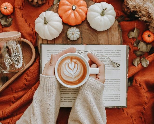 kawa w białej filiżance na tle otwartej książki obok małych dyń