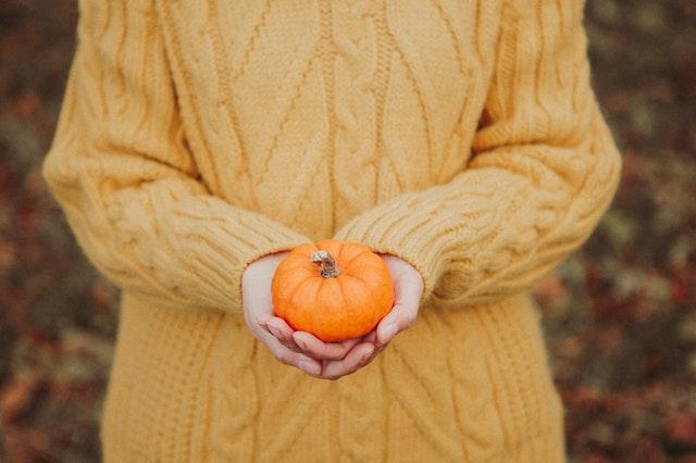 kobieta w żółtym swetrze trzyma przed sobą małą dynię