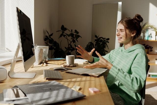 Dziewczynka w zielonej bluzie siedzi przy biurku