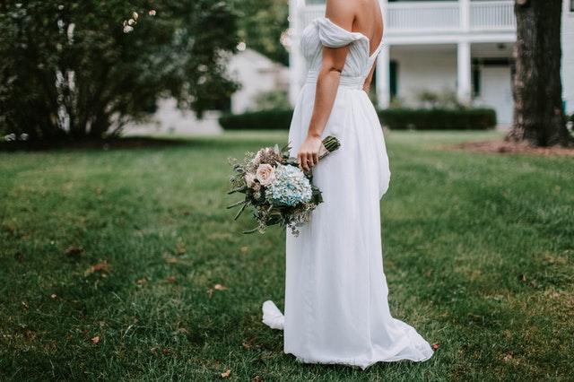 Panna młoda stoi bokiem w białej sukni na trawie