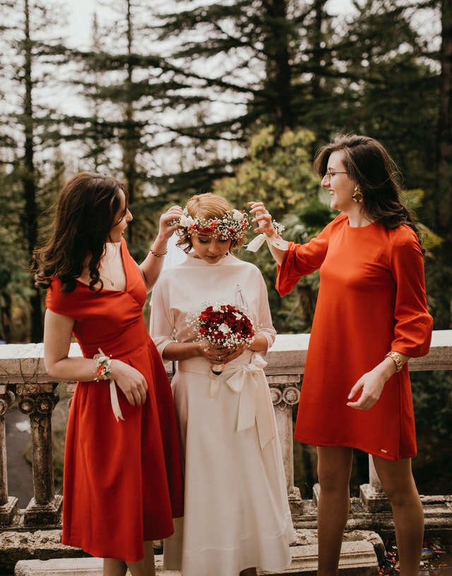 Panna młoda z wiankiem i w białej sukni stoi między dwoma kobietami w pomarańczowych sukienkach