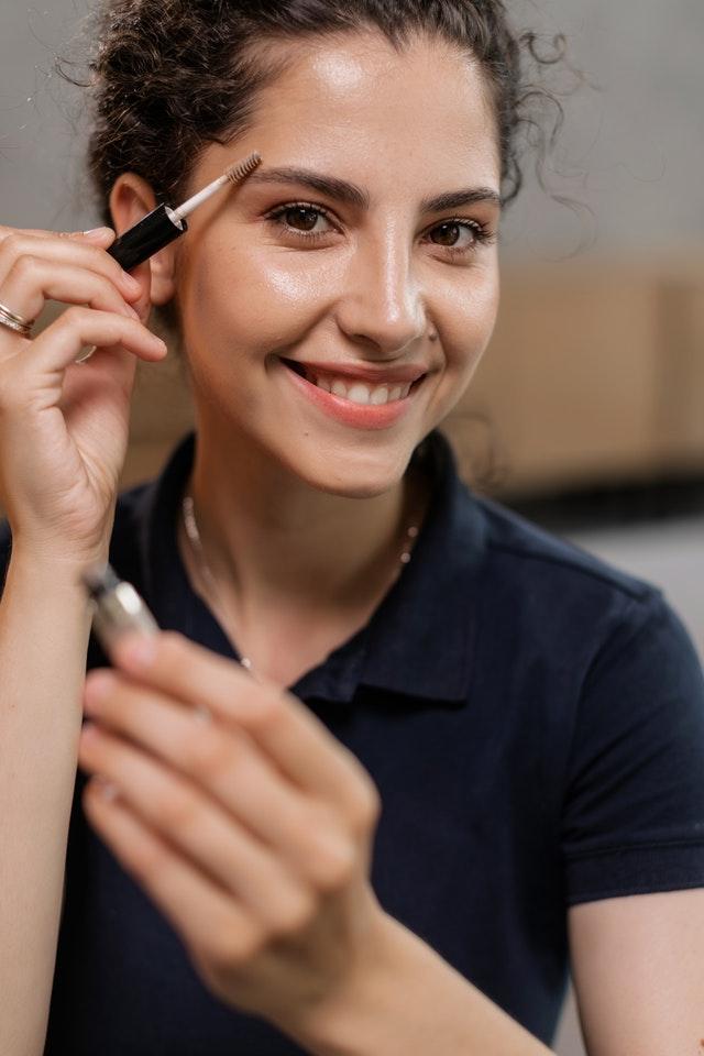 uśmiechnięta kobieta stylizuje brwi szczoteczką