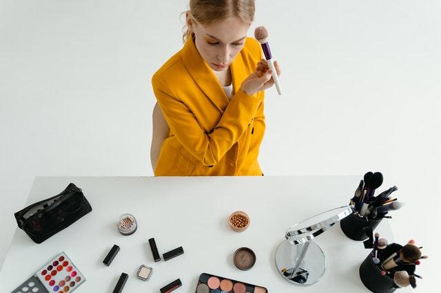 kobieta w pomarańczowej marynarce maluje się