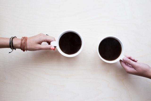 kawa czarna nalana do dwóch białych kubków, które trzymają dłonie