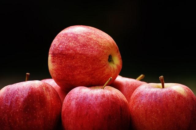 kilka czerwonych jabłek leżących na sobie na czarnym tle