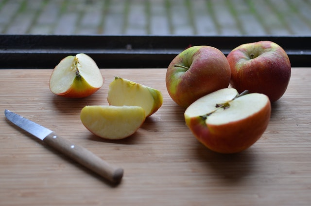 kilka przekrojonych jabłek leżących na blacie