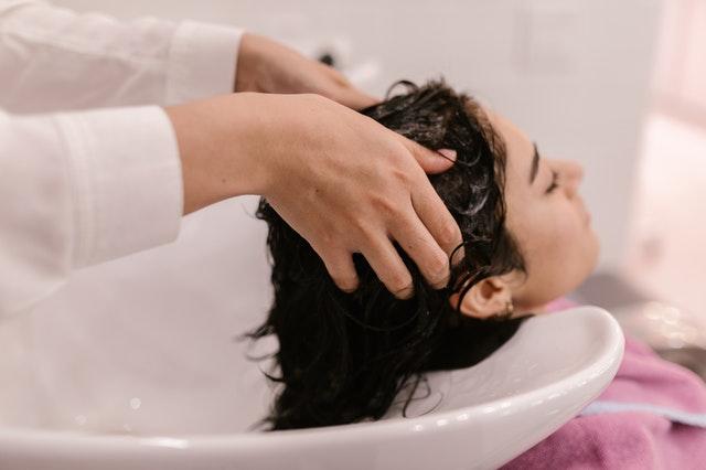 kobieta z mokrą głową w myjce fryzjerskiej