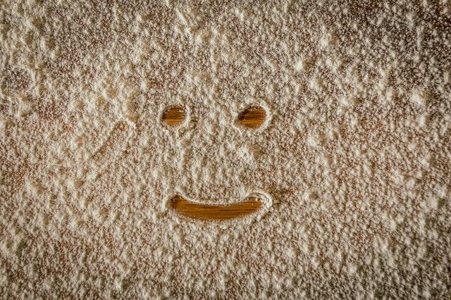 uśmiech narysowany na blacie z rozsypanej mąki