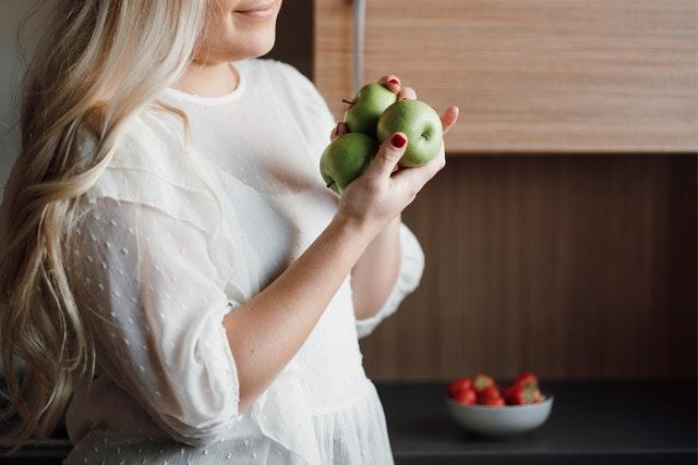 blondynka w rozpuszczonych włosach w białym golfie trzyma zielone jabłka