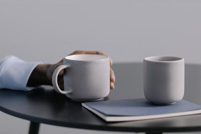 zbliżenie na biały kubek trzymany w dłoni na biurku